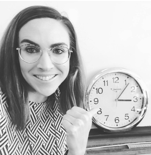 Nadia pointing at a clock that reads 3:07pm