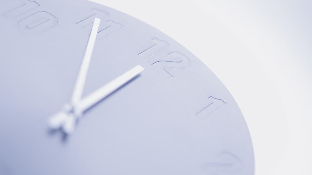 Image of blue clock on pale blue background. The time reads 11:55