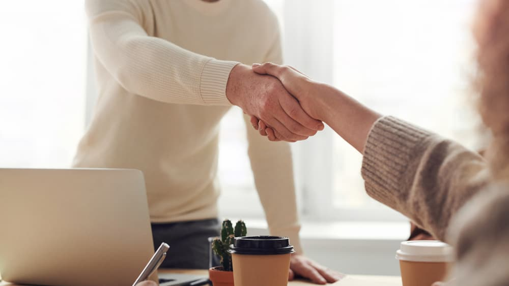 Two people shaking hands over coffee and laptop