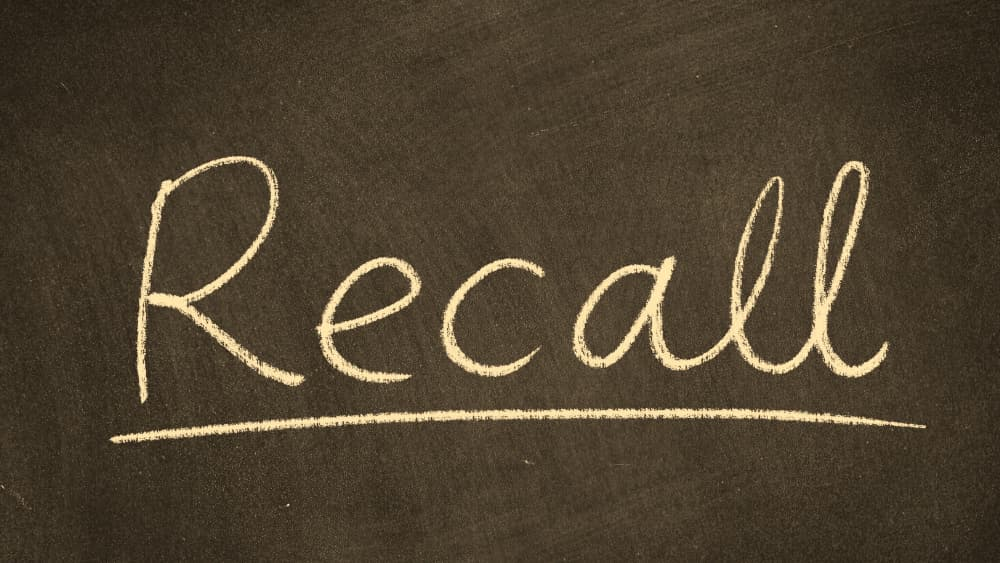 """Black chalkboard with word """"recall"""" written on it. Image is in sepia tone."""