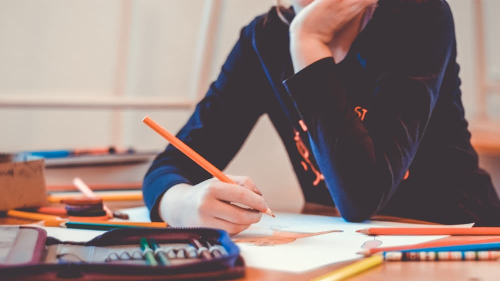 Image of student wearing navy shirt, holding orange pencil working. Pencils are scattered around the dest